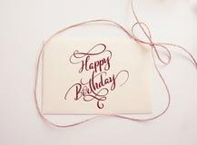 Ark av papper med lycklig födelsedag för pilbåge och för text Kalligrafibokstäver cabrioletkortclaus roliga greating lyckliga kan Arkivfoton