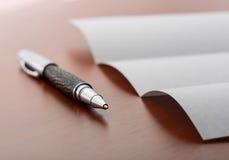 Ark av papper och pennan på skrivbordet Arkivfoto