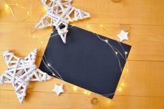 Ark för julbakgrundssvart av papper med stället för din text och vita jul stjärna och girland på en träguld Arkivfoto