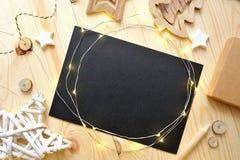 Ark för julbakgrundssvart av papper med stället för din text och vita jul stjärna och girland på ett trä Arkivfoto
