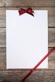 Ark för tomt papper med den burgundy pilbågen på den gråa träbakgrunden Royaltyfri Fotografi