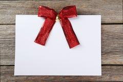 Ark för tomt papper med den röda pilbågen på träbakgrund Arkivfoto