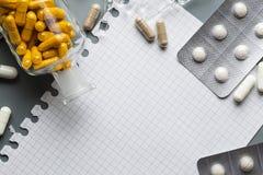 Ark för tomt papper och olika läkarbehandlingar på en grå bakgrund Royaltyfri Bild