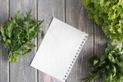 Ark och sammansättning av grönsaker på det gråa träskrivbordet Arkivfoton
