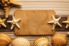 Ark, skal och sjöstjärna för tomt papper på sand arkivbilder