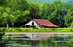 Arkansas Ozark`s Rustic Barn. Sits besides a tranquil pool.  Barn`s reflection shows weathered wood and rusting tin Stock Photography