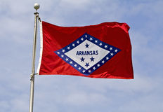 Arkansas State Flag. The Arkansas State Flag flying in the wind against a cloudy blue sky stock photo