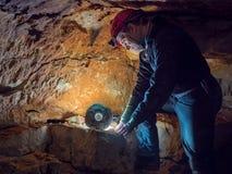 Arkeologblick p? stenhjulet exponerat av panelljuset i grottorna arkivfoto