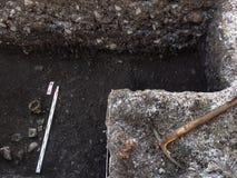 Arkeologisk utgrävning med för skalle som halvt fortfarande begravas i jordningen och hjälpmedlen som beside ligger royaltyfria foton