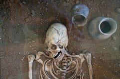 Arkeologiska utgrävningar av en forntida mänsklig skelett- och människaskalle royaltyfri bild