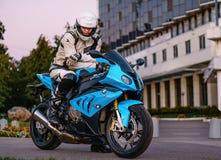 ARKHANGELSK, FEDERACIÓN RUSA - 4 DE SEPTIEMBRE: Motorista en una bici del deporte de BMW S 1000 RR adentro en la puesta del sol,  Fotografía de archivo libre de regalías