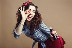Arkhangelsk Ryssland - januari 10, 2017: Lyckliga härliga Pin Up Girl Holding Cup av glasflaskan som reko symbol och att ge sig Royaltyfria Bilder