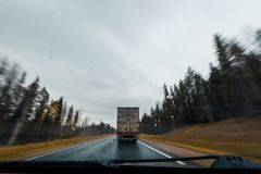 Arkhangesk,俄罗斯- 2017年10月11日:在秋天森林公路的卡车高速驾驶 挡风玻璃看法  库存图片