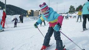 Arkhyz РОССИЯ - 25-ОЕ ЯНВАРЯ 2019: Активное катание на лыжах девушки в горах Гонка лыжи для маленьких ребеят Маленький лыжник уча видеоматериал