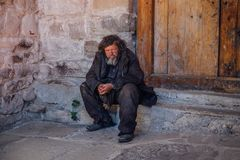 Arkhyz, Karachay-Cherkessia, Russia - April 26, 2017: Shabby homeless sad old man is sitting on the threshold of the church.  Stock Image