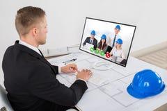 Arkitekt Attending Video Conference i regeringsställning Royaltyfri Fotografi