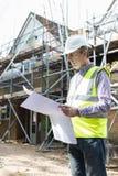 Arkitekt On Building Site som ser husplan Fotografering för Bildbyråer