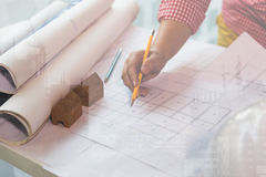 Arkitekt eller tekniker som i regeringsställning arbetar med ritningar, Constru arkivbilder