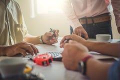 Arkitekt- eller teknikerlag som arbetar med ritningar som i regeringsställning bygger hjälpmedel för teknik för konstruktion för  royaltyfri bild