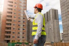Arkitekt i hardhat som pekar med rullande ritningar på byggnad Arkivfoton