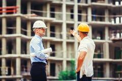 Arkitekt och byggmästare som diskuterar på konstruktionsplatsen Royaltyfri Bild