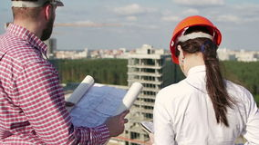 Arkitekt och tekniker som ser på projekt stock video