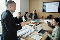 Arkitekt Showing Miniature Building på affärsmötet med klienten arkivbild