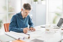 Arkitekt som arbetar i hans kontor Arkivbilder