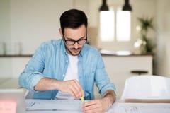 Arkitekt som arbetar på den hemmastadda kontorstabellen för plan Royaltyfria Bilder