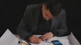 Arkitekt som arbetar på ritning på svart bakgrund stock video