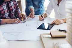 Arkitekt som arbetar på ritningen, teknikermöte som arbetar med PA Arkivfoto