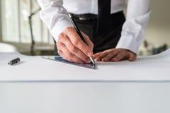 Arkitekt som drar ett utkast på ett papper arkivbild