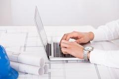 Arkitekt som i regeringsställning använder bärbara datorn Arkivbild