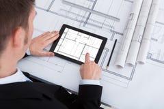 Arkitekt som i regeringsställning använder den digitala minnestavlan på ritning Fotografering för Bildbyråer