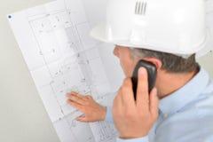 Arkitekt som kontrollerar plan med klienten över telefonen Arkivfoto