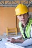 Arkitekt som ser kameran, medan arbeta med ritningar på konstruktionsplatsen Royaltyfri Bild