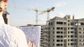 Arkitekt som ser på projekt på konstruktionsplats stock video