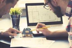 Arkitekt som visar modellen för nytt hus till kunden på kontoret Royaltyfri Bild