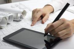 Arkitekt Working On Blueprint Arkitektarbetsplats - arkitektoniskt projekt, ritningar, linjal, räknemaskin, bärbar dator och royaltyfri foto
