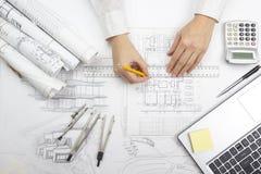 Arkitekt Working On Blueprint Arkitektarbetsplats - arkitektoniskt projekt, ritningar, linjal, räknemaskin, bärbar dator och Royaltyfria Foton