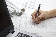 Arkitekt Working On Blueprint Arkitektarbetsplats - arkitektoniskt projekt, ritningar, linjal, räknemaskin, bärbar dator och royaltyfri bild