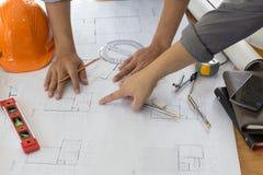 Arkitekt Working On Blueprint Arkitektarbetsplats - arkitektoniskt projekt, ritningar, linjal, räknemaskin, bärbar dator och avde Royaltyfri Fotografi