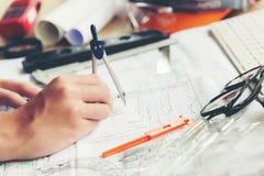 Arkitekt Working On Blueprint Arkitektarbetsplats Teknikerhj?lpmedel och s?kerhetskontroll, ritningar, linjal, orange hj?lm, radi fotografering för bildbyråer