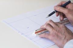 Arkitekten drar översikten av huset med pennan, linjalen och papper royaltyfria bilder