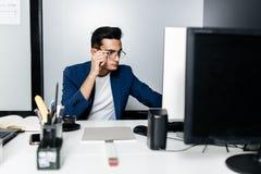 Arkitekten för den unga mannen i iklädda exponeringsglas en affärsdräkt sitter på ett skrivbord framme av en dator i kontoret royaltyfri bild