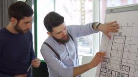 Arkitekten flyttar hans hand över designen av byggnaden arkivfoton