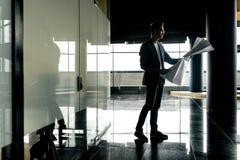 Arkitekten i stilfull kläder rymmer arket med teckningen i hans hand och samtal vid telefonen på bakgrunden av ett modernt expone royaltyfri bild