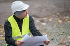 Arkitekten som bär en vit hjälm som kontrollerar kontoret, gör en skiss av på konstruktionsplats Fotografering för Bildbyråer