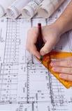 Arkitekten som drar rullar och, planerar ritningar arkivbild