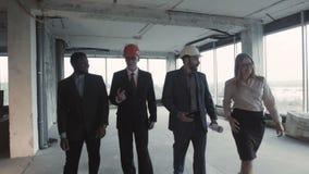 Arkitekter diskuterar förverkligande av projektet av att möblera en kontorsbyggnad i ett perspektivområde stock video
